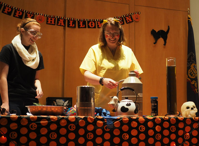 "Biochemistry major Zoe Waizenegger assists Dr. Julie Belanger, associate professor of chemistry, during King's annual Halloween exhibition for children, ""Things That Go Boom in the Night."""