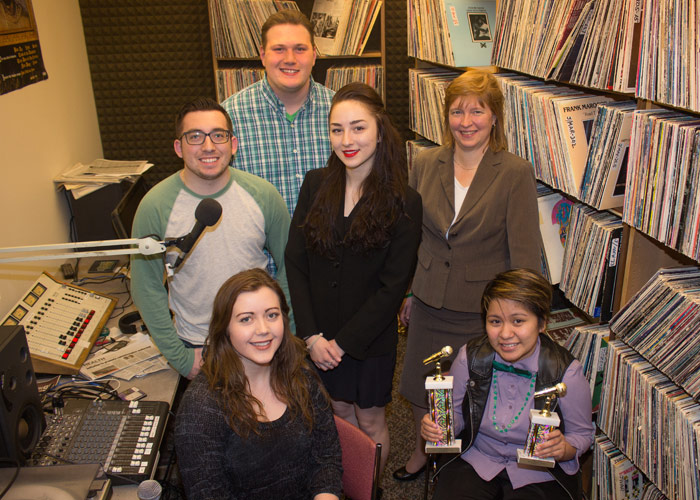 Pictured seated, from left, is Brielle Warren, news reporter, and Kristina Atienza, station manager.  Pictured in second row, from left, is Nicholas Rotondo, news director, Therese Roughsedge, music director, and Sue Henry, station manager.  Pictured in b